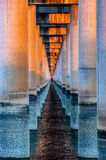 Sunset between columns that form the base of a bridge on the sea Royalty Free Stock Photography