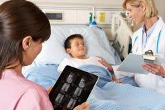 Infirmière à l'aide de la tablette de Digitals tout en rendant visite au patient Photographie stock