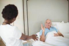 Infirmière agissant l'un sur l'autre avec l'homme supérieur sur le lit image libre de droits