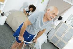 Infirmière aidant l'homme plus âgé avec le cadre de marche Photo libre de droits