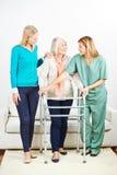 Infirmière aidant la femme supérieure avec le marcheur Photographie stock