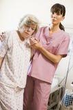 Infirmière aidant le femme aîné à marcher photographie stock