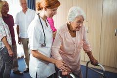 Infirmière aidant une femme retirée à marcher Images stock