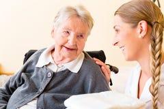 Infirmière apportant des approvisionnements à la femme dans la maison de retraite Photographie stock libre de droits