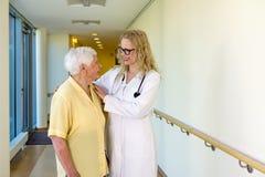 Infirmière Assisting Elderly Woman marchant au couloir Image libre de droits
