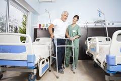 Infirmière Assisting Male Patient en employant Walker At Rehab Center Photographie stock