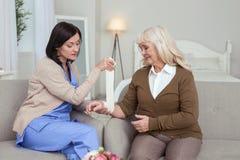 Infirmière attentive attachant du ruban adhésif vers le haut de la main de femme plus âgée Image libre de droits