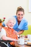 Infirmière avec la femme supérieure aidant avec le repas Image libre de droits