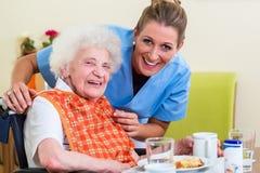 Infirmière avec la femme supérieure aidant avec le repas Photo stock