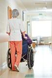 Infirmière avec le patient plus âgé dans le fauteuil roulant Photo stock