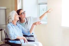 Infirmière avec son patient dans le fauteuil roulant Image libre de droits