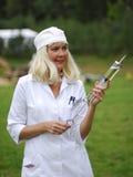 Infirmière avec une seringue colossale Photo stock