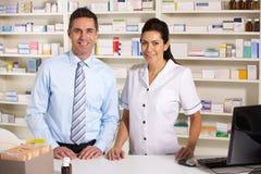 Infirmière BRITANNIQUE et pharmacien travaillant dans la pharmacie Photographie stock libre de droits