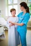 Infirmière consolant un patient dans la salle d'hôpital Images libres de droits