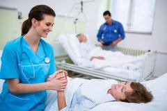 Infirmière consolant un patient dans la salle d'hôpital Images stock