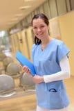 Infirmière dans l'hôpital se tenant avec le dossier patient Photo stock