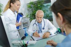 Infirmière de consultation patiente de docteur attendant pour sélectionner la prescription Photo libre de droits
