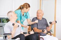Infirmière de Geratric motivant les hommes supérieurs en physiothérapie images libres de droits