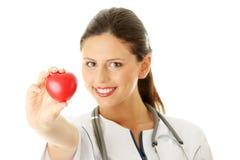 Infirmière de jeunes avec le coeur dans sa main Image stock