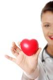 Infirmière de jeunes avec le coeur dans sa main Photos stock