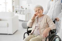 Infirmière de jeunes et femme agée handicapée dans le fauteuil roulant Photos libres de droits