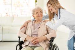 Infirmière de jeunes et femme agée handicapée dans le fauteuil roulant Images libres de droits