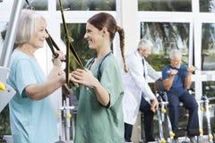 Infirmière de sourire Assisting Senior Woman avec la bande Exerci de résistance Photo stock