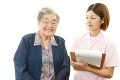 Infirmière de sourire avec dame âgée Image libre de droits