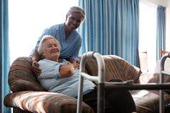 Infirmière de sourire avec la femme supérieure au sofa dans la maison de repos Photo stock