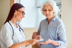 Infirmière de sourire avec son patient Image stock