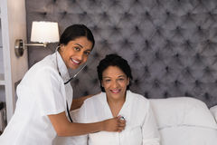 Infirmière de sourire examinant la femme mûre se reposant sur le lit à la maison image libre de droits