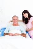 Infirmière de sourire fixant le bâti d'un patient aîné Images stock