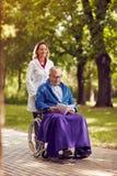 Infirmière de sourire poussant l'homme plus âgé dans le fauteuil roulant tout en lisant la BO Images stock