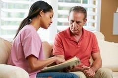 Infirmière discutant des enregistrements avec le patient mâle supérieur images stock