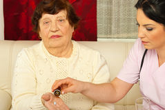Infirmière donnant des médecines à la femme âgée Photographie stock