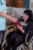 Infirmière donnant le livre à la femme handicapée Photographie stock