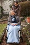 Infirmière et aîné dans le fauteuil roulant Photographie stock libre de droits