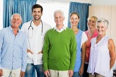 Infirmière et aînés se tenant ensemble Photo stock