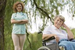 Infirmière et femme supérieure sur un fauteuil roulant dans le jardin Image stock