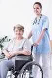 Infirmière et femme sur un fauteuil roulant Photos stock