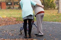 Infirmière et handicapé avec le marcheur Photos stock