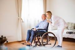 Infirmière et homme supérieur dans le fauteuil roulant pendant la visite à la maison Photos libres de droits