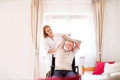 Infirmière et homme supérieur dans le fauteuil roulant pendant la visite à la maison Photographie stock