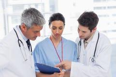 Infirmière et médecins regardant ensemble un dossier image stock