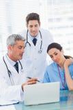 Infirmière et médecins travaillant ensemble sur un ordinateur portable Photos libres de droits
