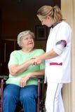 Infirmière et patient aîné dans un fauteuil roulant Image stock