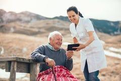 Infirmière et patient supérieur handicapé à l'aide du comprimé de chiffre extérieur Images libres de droits