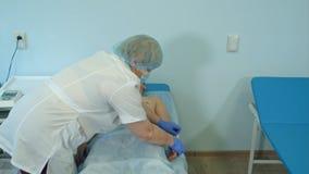 Infirmière expérimentée préparant le patient masculin pour l'électrocardiographie Photos stock