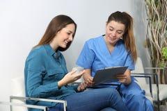 Infirmière expliquant l'acte médical à un patient photo stock