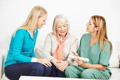 Infirmière expliquant le dosage de médecine pour la femme supérieure photographie stock